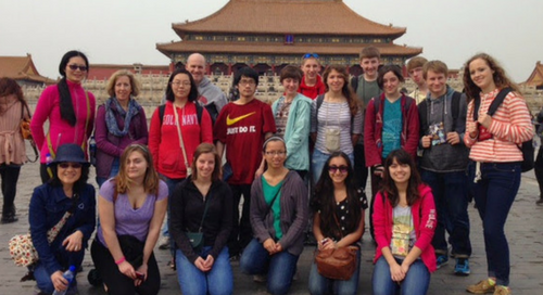 The Cecilia Ensemble (comprised of young students), Tour Managers, and chaperones posing for a group photo in front of a large temple in China