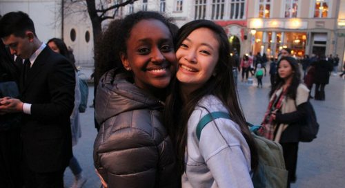 Two middle school-aged students hugging each other and smiling for the camera in the middle of a town square in the evening