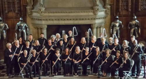 The Metropolitan Flute Orchestra in formal black attire holding their instruments, some of which are as tall as or taller tham them, in an ornately decorated hall with knights' armor as decoration in the background