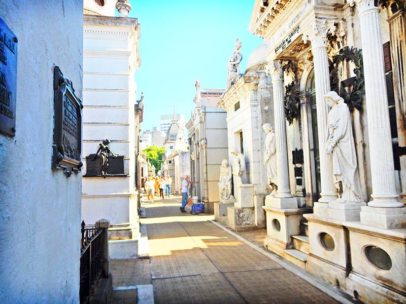 Alley way at Recoleta Cemetary, with both sides flanked by small but elaborate buildings featuring Greek columns, marble bases, brass plaques, and stone statues