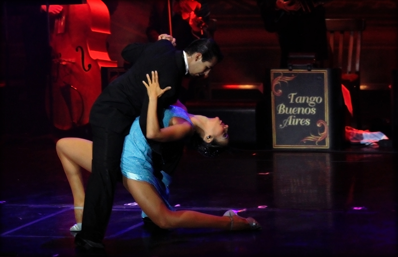 Male and female tango dancers dancing in Buenos Aires with strings players performing in the background