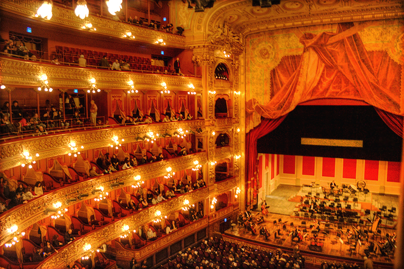 Large opera house with elaborate gold decor and red stage curtains, with an orchestra setting up on stage as the audience members find their seats
