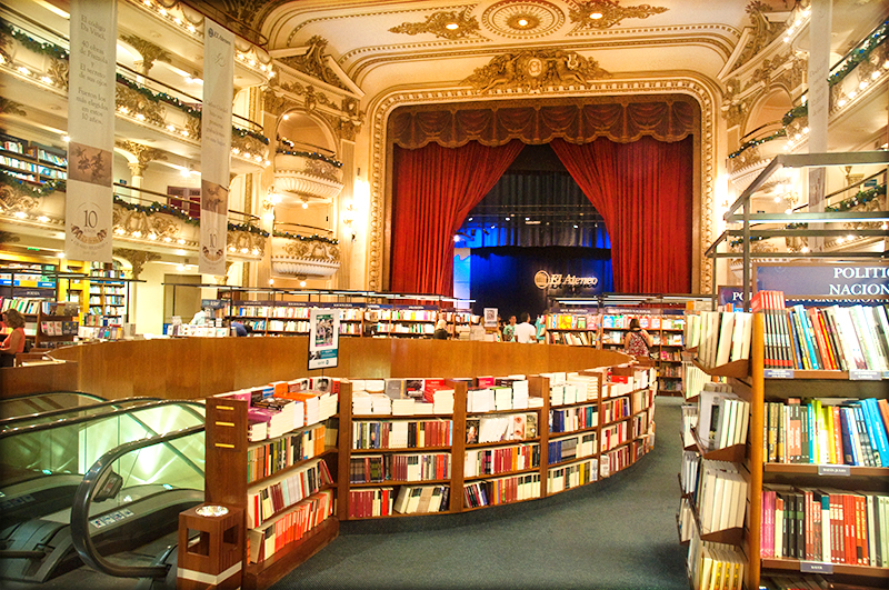 Brightly-lit bookstore converted from an old opera house, with red stage curtains and elaborate gold decor still intact; escalators leading from the ground floor to the main story which is lined with shelves of books everywhere