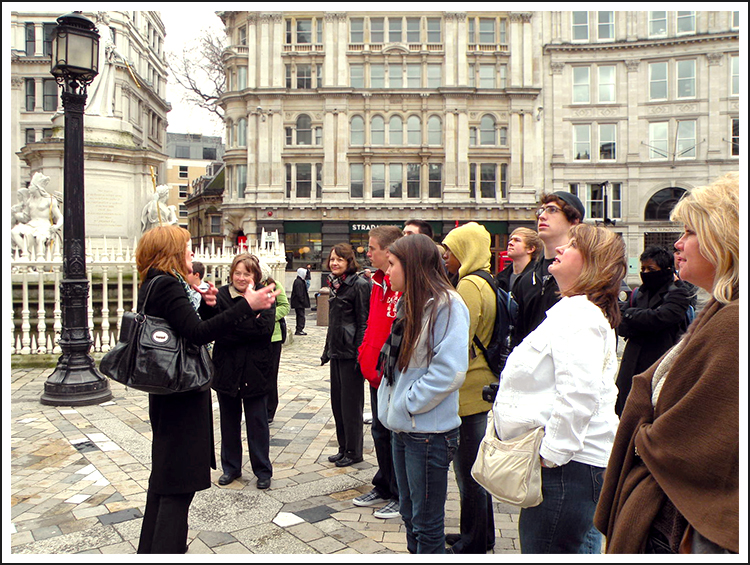Encore Tour Manager giving a city tour to passengers sightseeing in a European town square