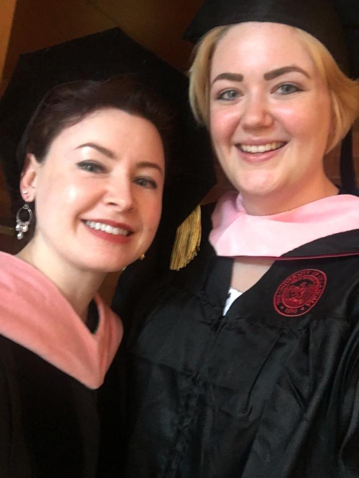 Author and a colleague taking a selfie together wearing graduation robes and hats