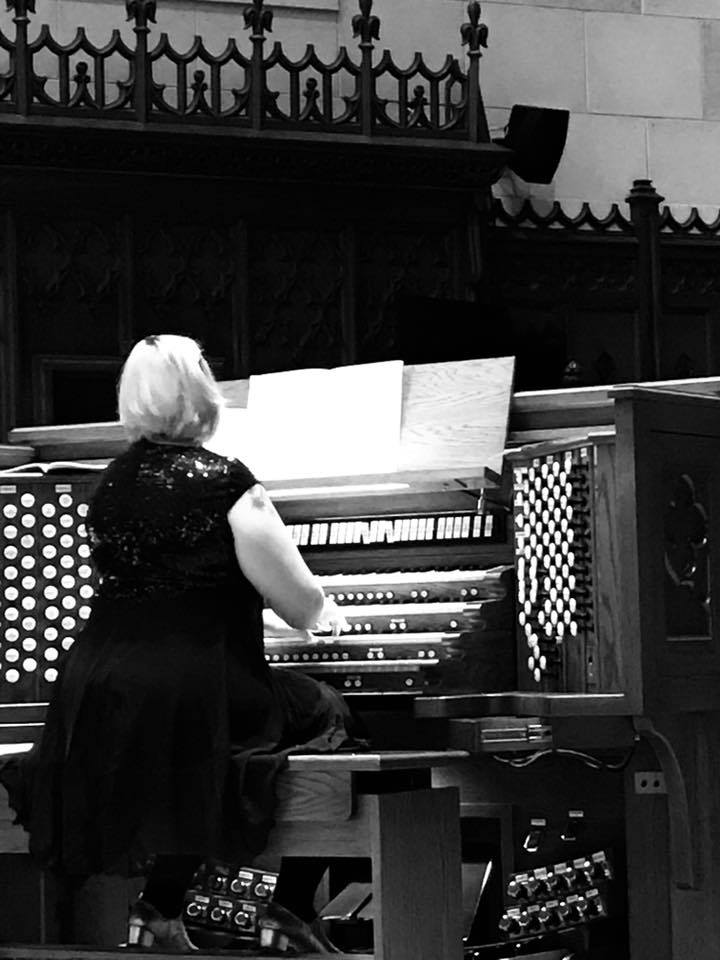 Author in a formal black dress playing an organ in a church setting