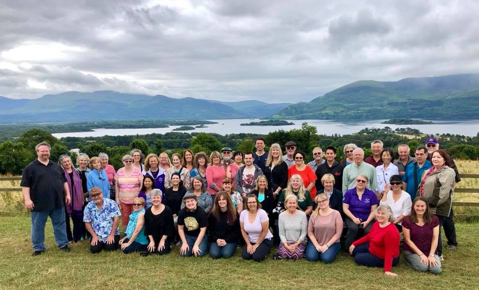 The California Central Coast Chorale posing for a group photo in a beautiful green landscape in Ireland, with calm waters and blue mountains in the background under a cloudy sky