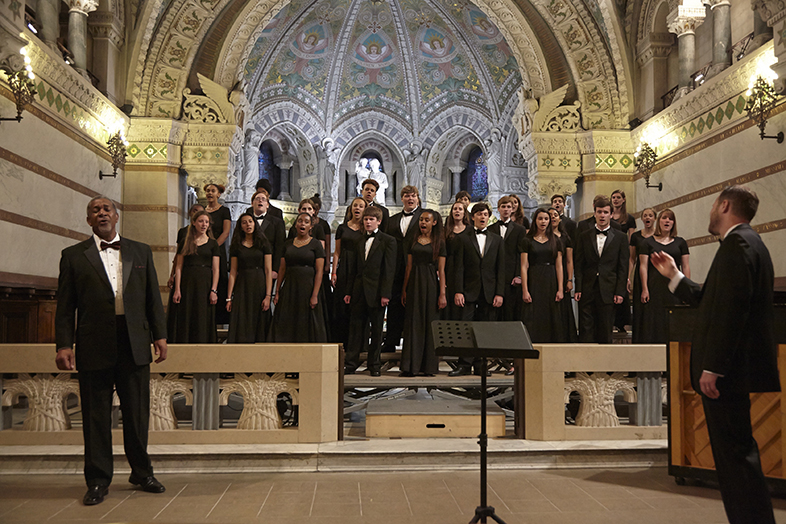 Choir in all-black formal clothing singing passionately in a cathedral setting