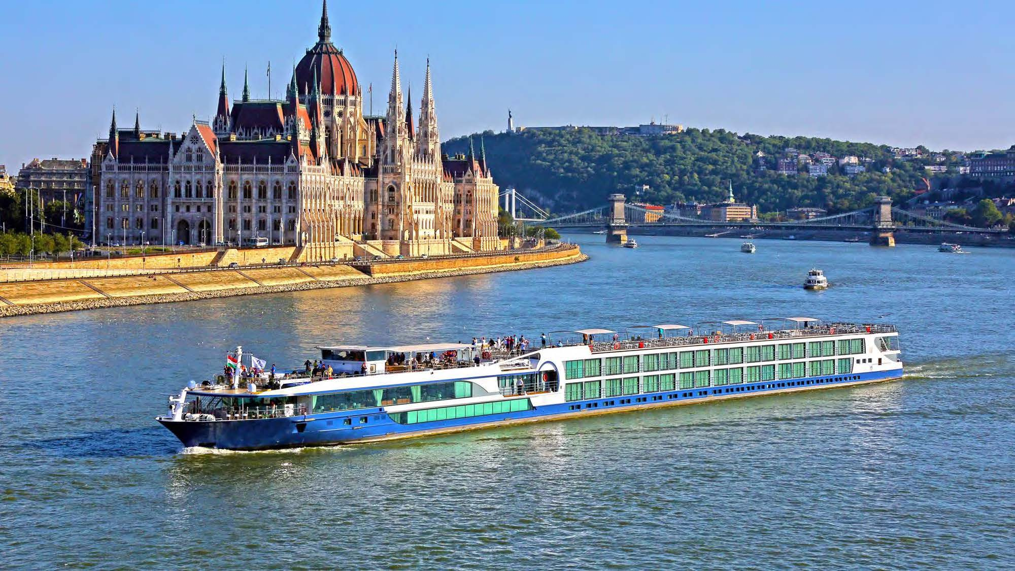 A cruise ship on the Danube River coasting by the Hungarian Parliament Building