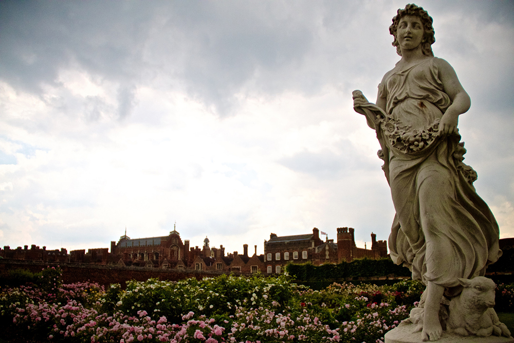 Statue of standing robed woman in Hampton Court Palace gardens under a cloudy sky | Photo Credit: traveljunction/Flickr