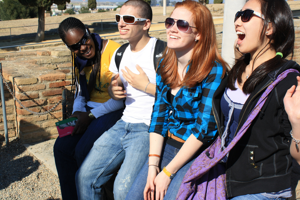 Four students wearing sunglasses sitting outdoors and socializing