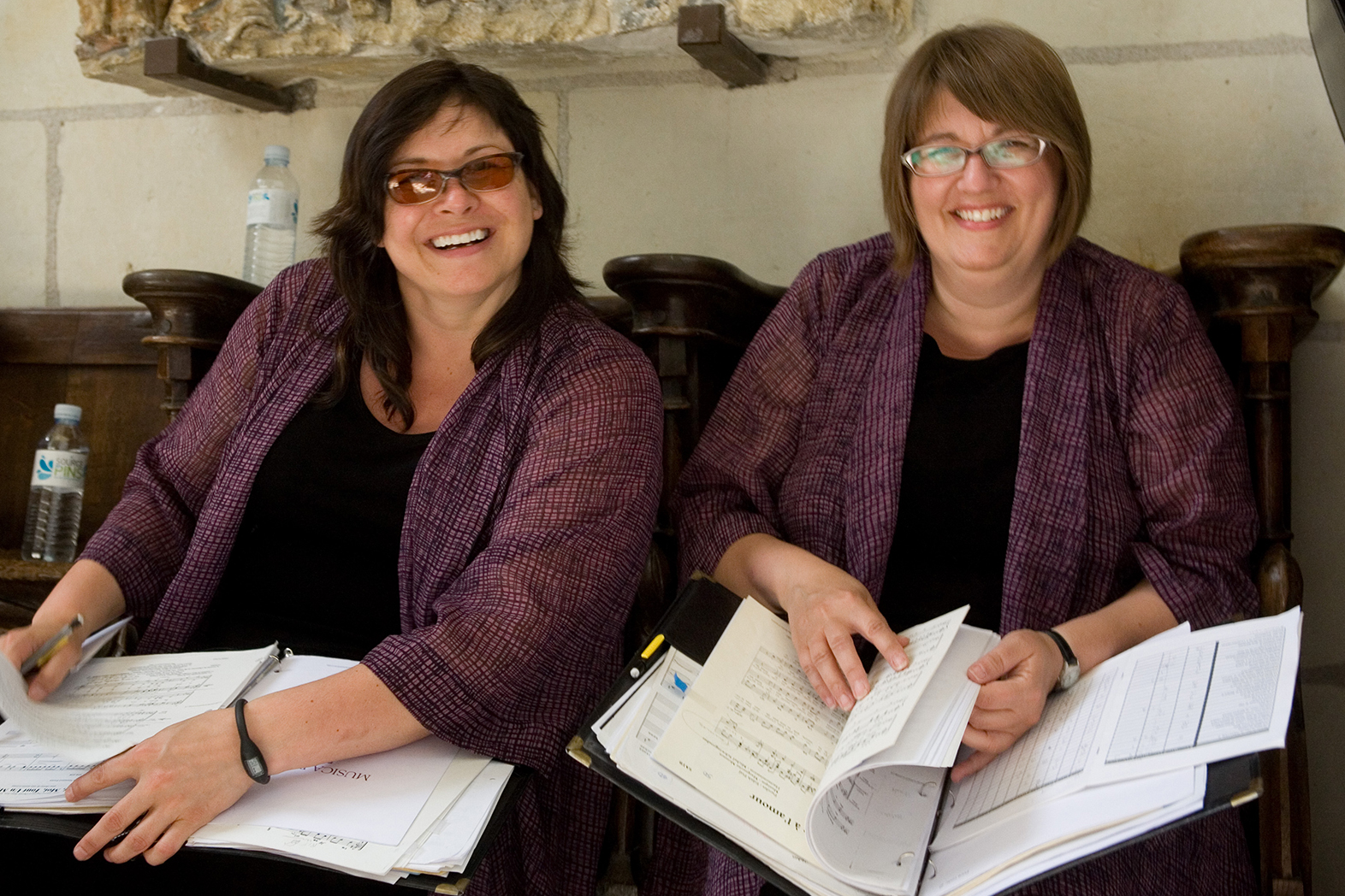 Two choir members in matching ensemble attire sitting on a pew in a church with their music binders on their laps, smiling and laughing for the camera