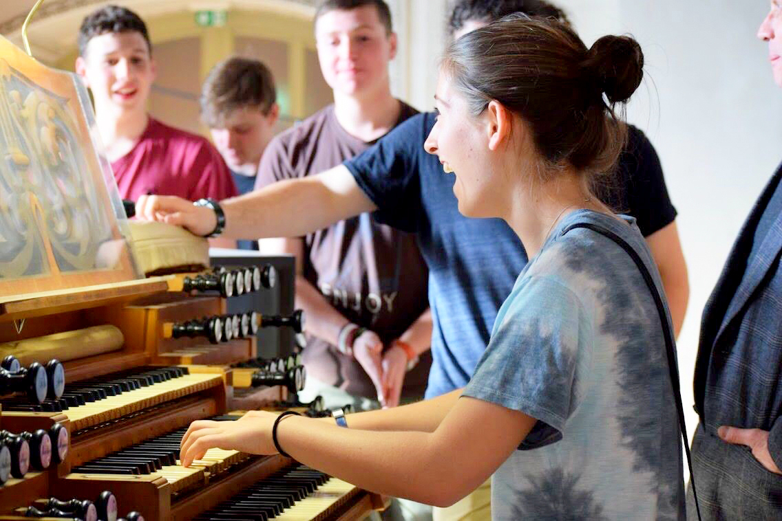 Music teacher singing and playing an organ surrounded by students