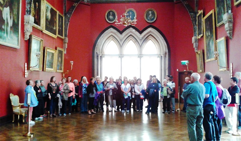 Great Hall, Kilkenny Castle - adult choir singing in the Great Hall of Kilkenny Castle, a high-ceilinged space with red walls, hardwood floor, and fine decor