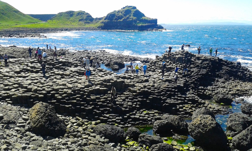 Giant's Causeway - large rocky coastline with bright blue water and grassy hills