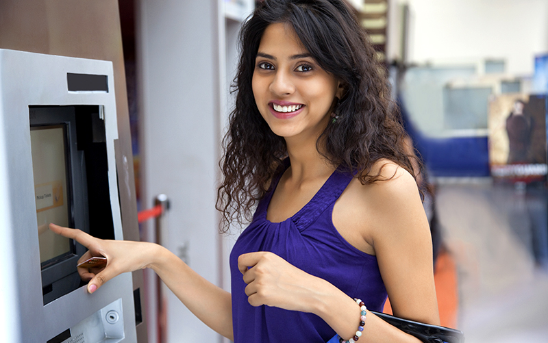 Smiling woman at automated teller machine (ATM)
