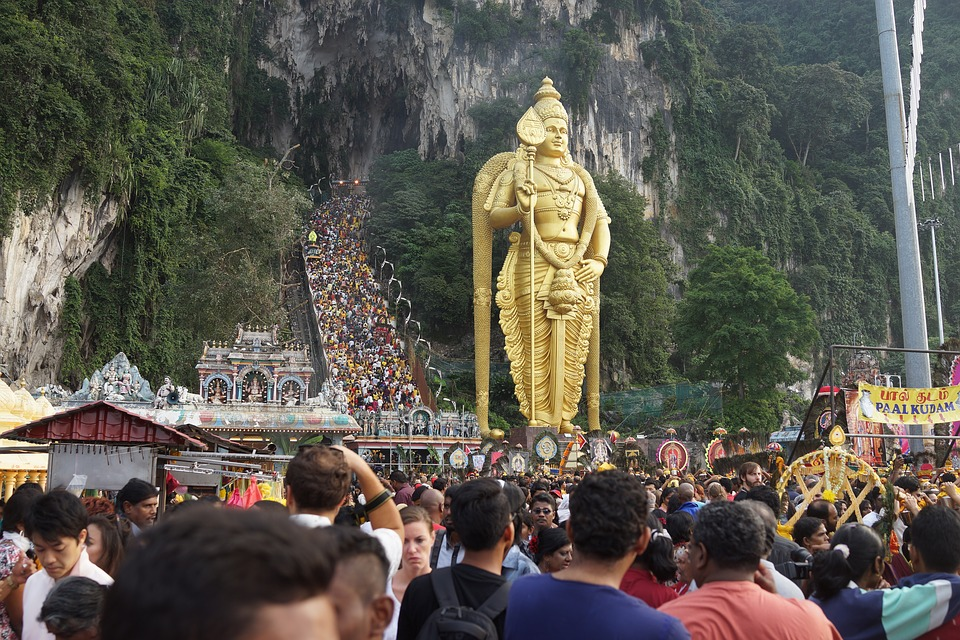 Large crowds of people gather at the Batu Caves, a limestone hill with a series of caves and cave temples in Malaysia. In front of the hill is a massive golden statue of Kartikeya, the Hindu god of war and victory.