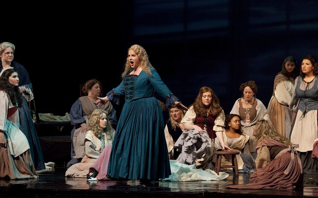 Opera singer in dark teal 18th-century Dutch-style dress performing on stage with numerous other cast members sitting behind and around her
