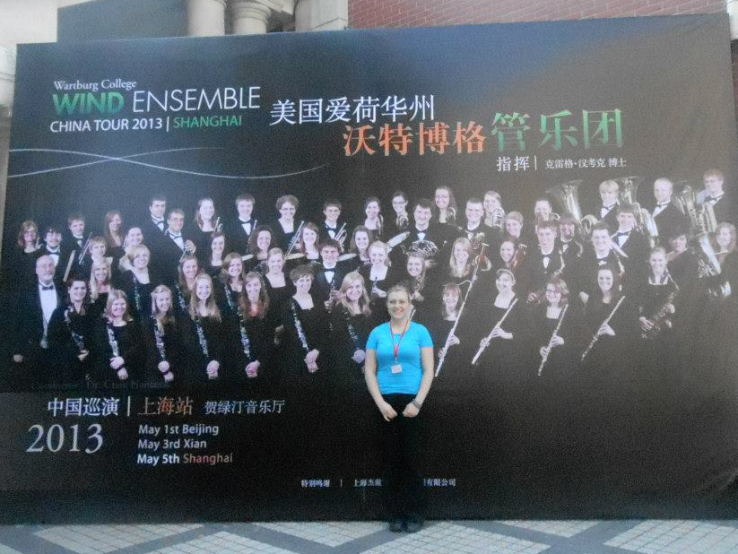 Kate standing in front a large mural-sized poster advertising the Wartburg College Wind Ensemble's 2013 China Tour in Shanghai in both English and Chinese, featuring the ensemble members holding their instruments on a black backdrop