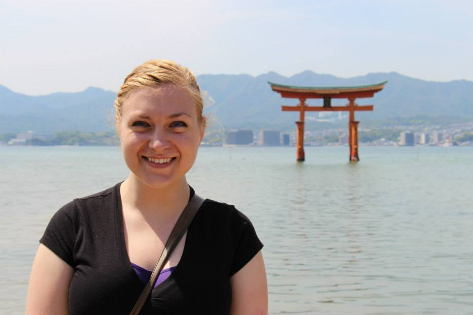 Kate smiling for the camera with a red torii gate (a traditional Japanese gate) appearing to float over the calm body of water behind her; Japanese mountains and buildings faintly visible in the background