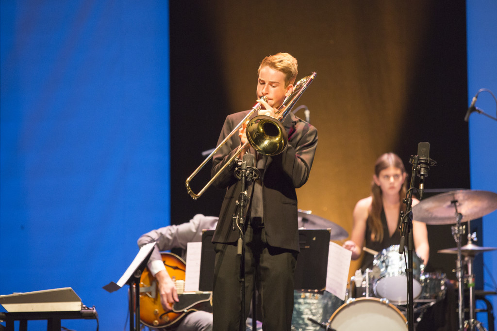 Trumpet player in jazz band performing on stage with guitarist and drummer in background