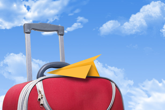 Red suitcase with yellow paper airplane resting on top of; background of a blue sky