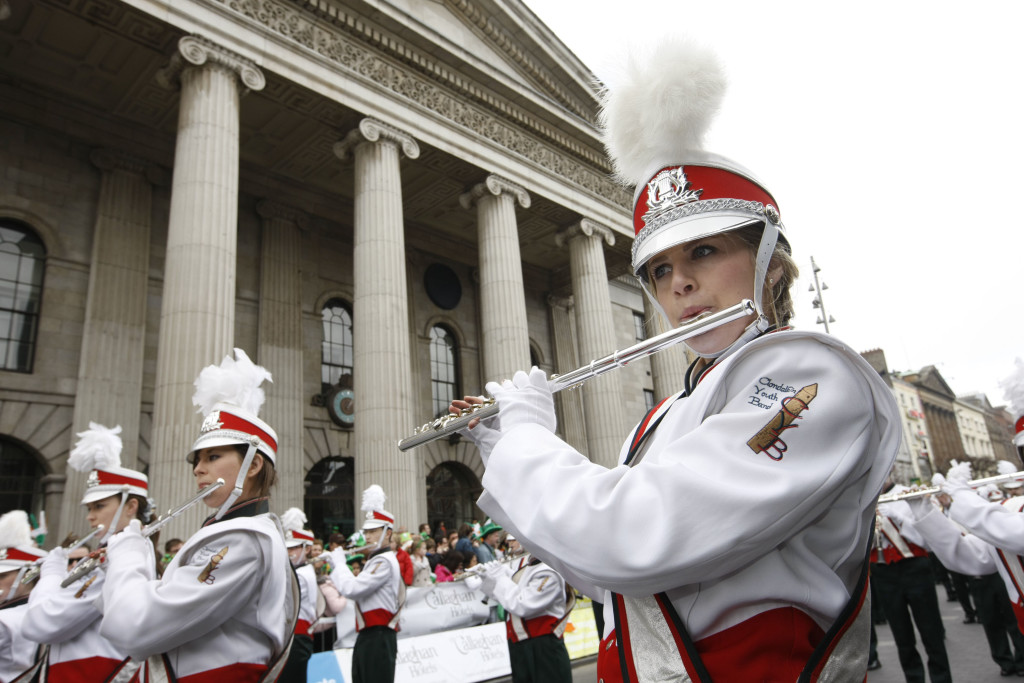 Marching band members in uniform playing the flute in the parade at the St. Patrick's Festival in Dublin, Ireland
