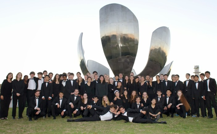 Orchestra in formal attire posing for a group photo in front of the Floralis Genérica (a massive metal sculpture of a flower) in Argentina