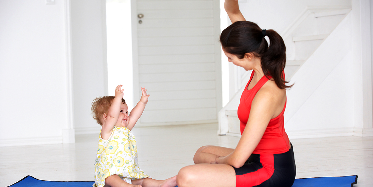 Mother and baby doing yoga together and having lots of fun