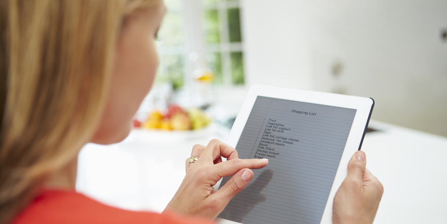 Woman looking at shopping list on her tablet
