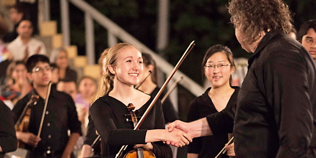 Young violinist shaking hands with her orchestra director and smiling