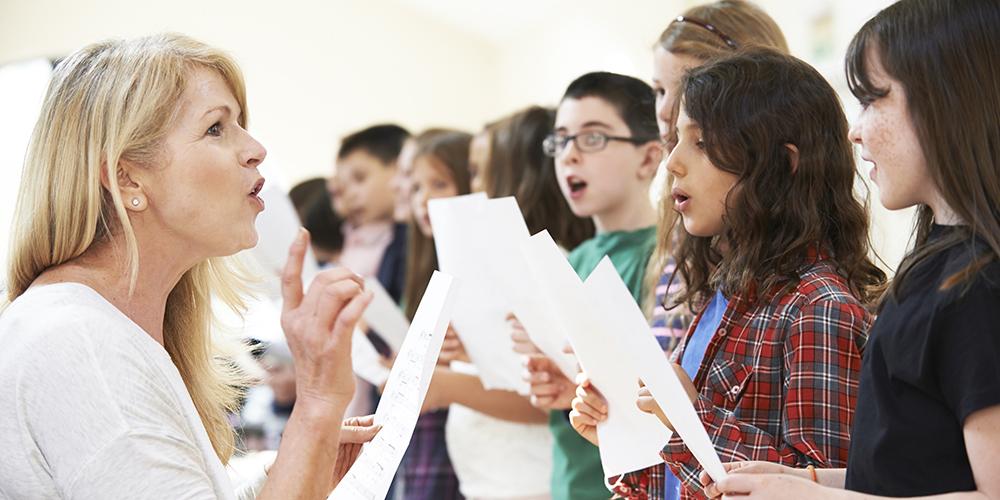 Choir director teaching young choir students