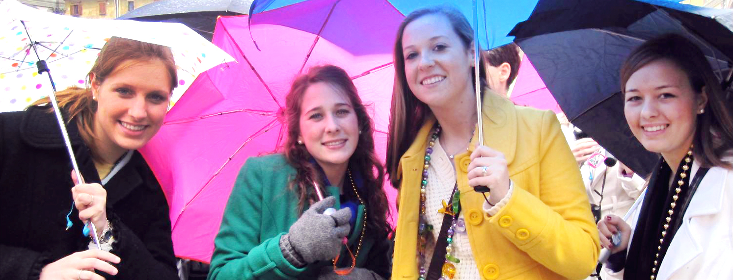 Members of a group on an Encore Tour holding colorful umbrellas and smiling for the camera