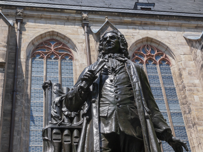 Bronze statue of Bach in front of a building with Gothic windows