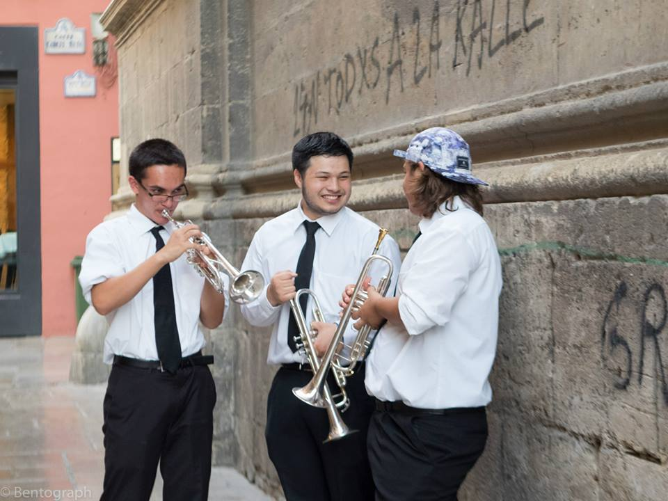 Trumpet players holding their instruments and having a good time chatting with each other in front of the Plaza de las Pasiegas at the Granada International Music Festival in Spain