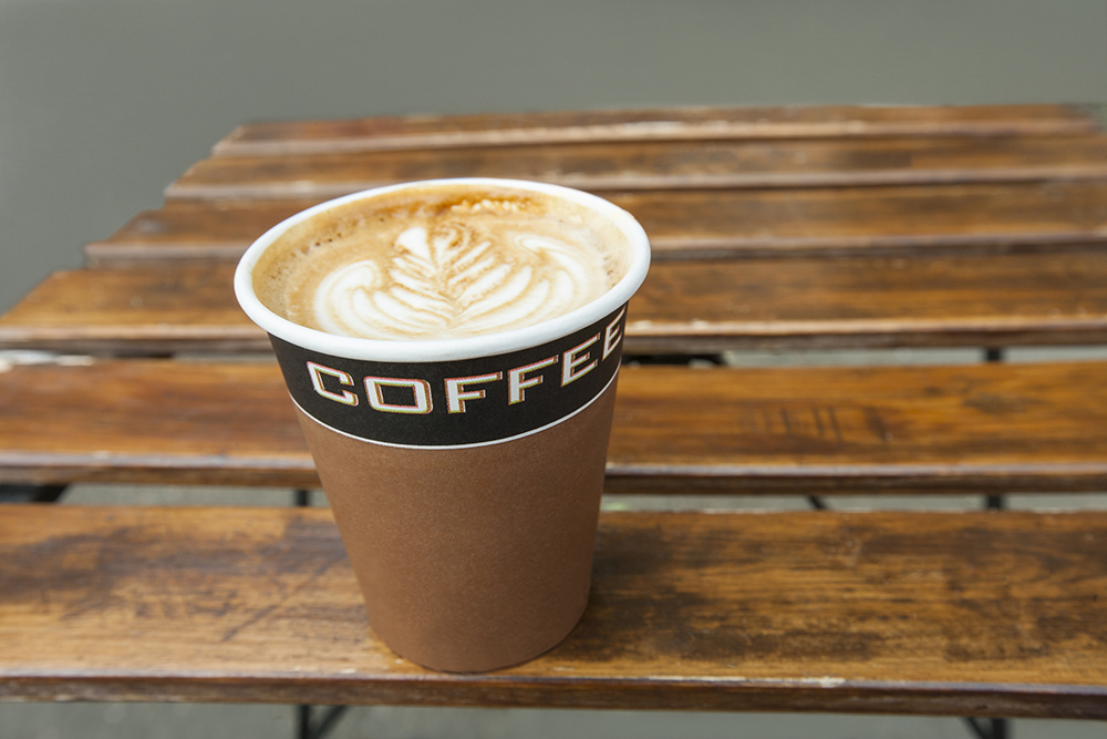 Coffee with frothy leaf latte art in paper cup on wood pallet table