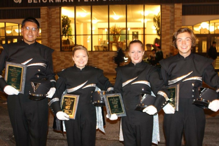 Goshen High School Band members in uniform holding awards and smiling at the camera