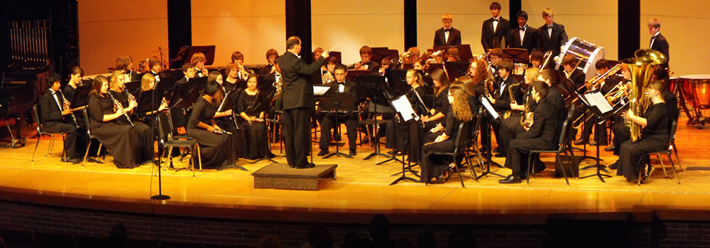 Goshen High School Wind Ensemble performing on stage in a concert hall and being conducted by band director Tom Cox