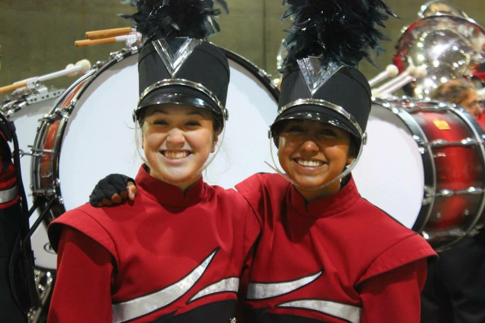 Goshen High School Marching Band members in uniform and smiling at the camera with arms around one another; drums in background
