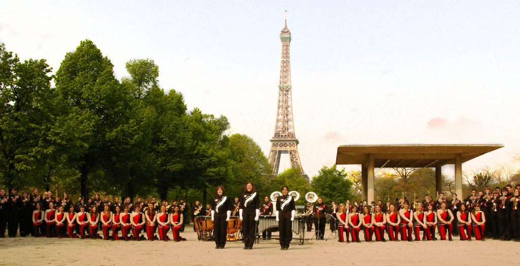 Marching band in uniform in Paris, France; Eiffel Tower standing tall in the background