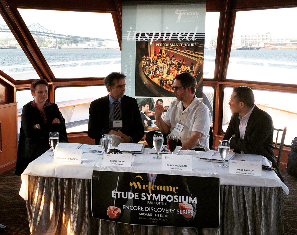 Four speakers in formal attire sitting on a table covered in white table cloth and with glasses of water and wine in front of them at the Encore Tours Etude Symposium; Boston Harbor visible in the background through the large window of the ship