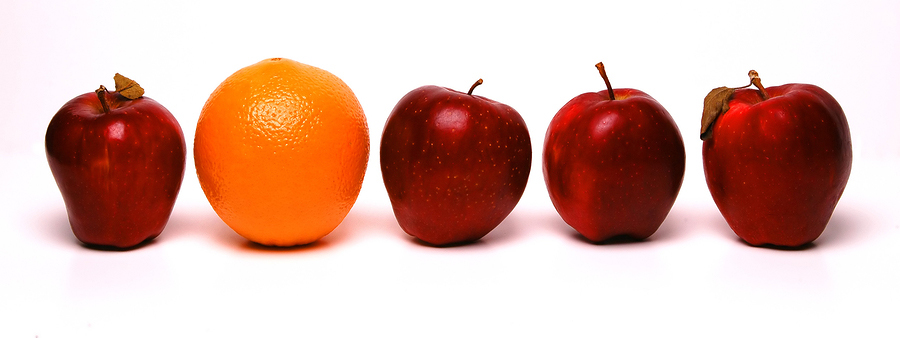 Row of red apples with a single naval orange in between