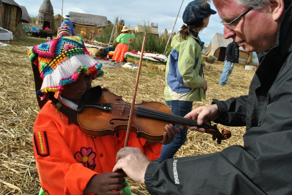 Teacher instructing child wearing colorful traditional clothing playing violin outdoors in a small village