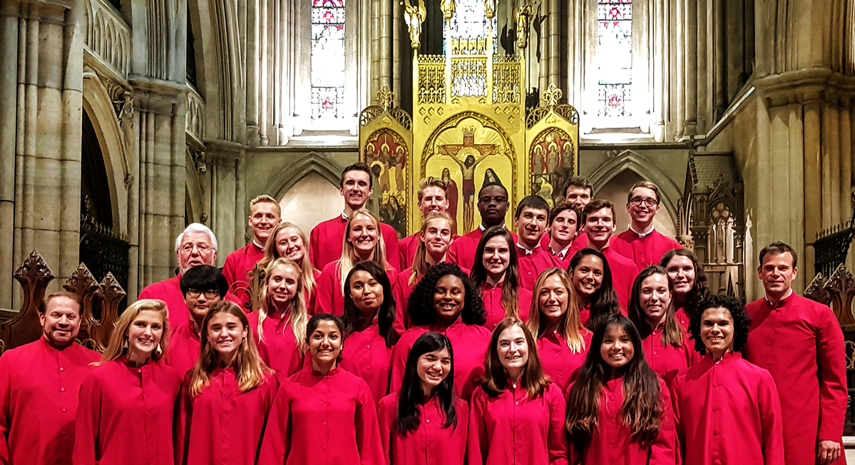 Taft School Collegium Musicum, a high school choir, dressed in red choir robes and smiling for the camera in front of a church altar