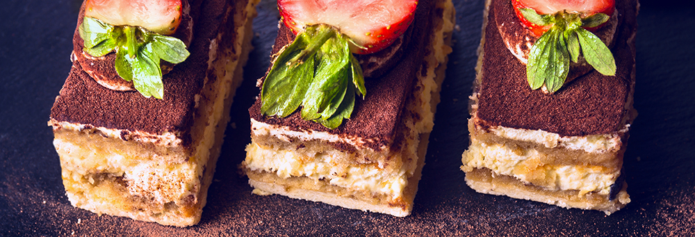 Three pieces of strawberry-topped tiramisu on wooden table