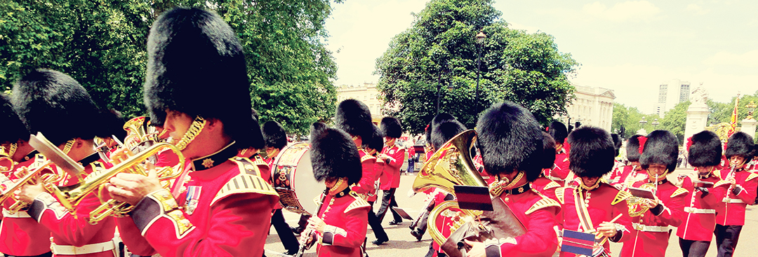 The Queen's Guard marching in front of Buckingham Palace while playing brass instruments and drums on a sunny summer day