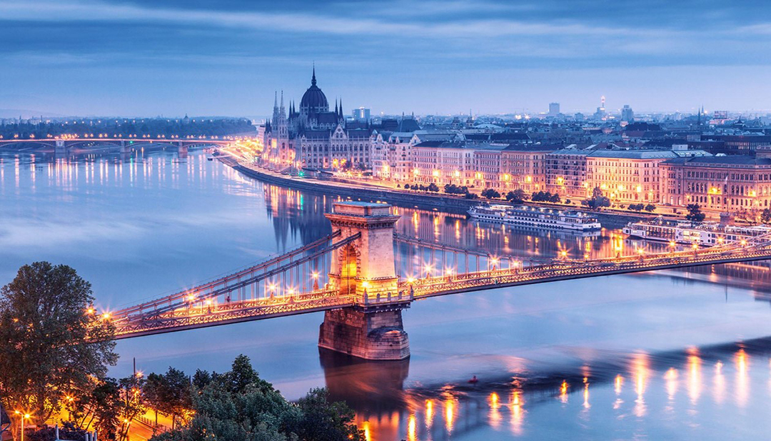 Széchenyi Chain Bridge in Budapest in the evening, with warm city lights reflected in the Danube River and the Budapest skyline visible in the background