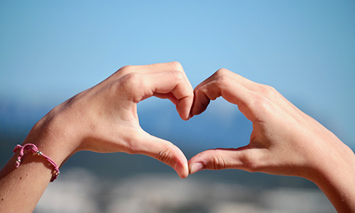 Hands making a heart shape, with a blue sky and blurry horizon in the background