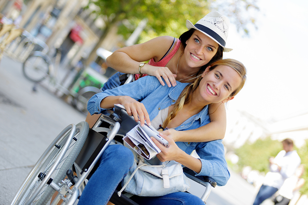 Two young women, one of whom is using a manual wheelchair and holding a brochure, smiling and sightseeing in a downtown area on vacation on a sunny day