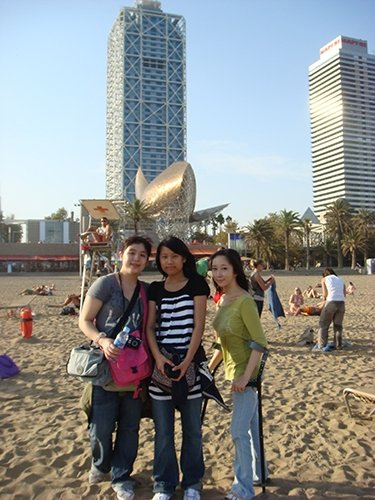 Blog post author Yuri Kim using black forearm crutches while posing for a photo with her two friends on a beach in Barcelona, Spain on a bright and sunny day